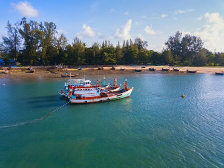 Aerial view of boats with natural forest trees, sand, tropical beach and waves rolling into the shore, Andaman sea, Phuket bay island in summer season, Thailand. Top view Banco de Imagens