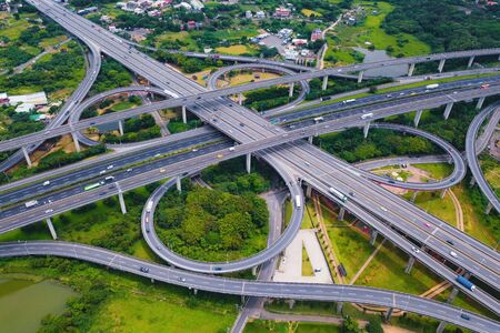 Aerial view of highway junctions. Bridge roads shape number 8 or infinity sign with green garden and trees in connection of architecture concept. Top view. Urban city, Taipei at sunset, Taiwan. Stock Photo