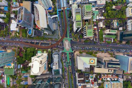 Aerial view of Sathorn intersection or junction with cars traffic, Bangkok Downtown. Thailand. Financial district and business centers in smart urban city. Skyscraper and high-rise buildings.