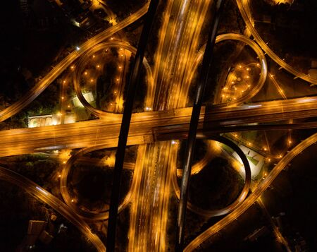 Aerial view of cars driving on highway junctions. Bridge roads shape number 8 or infinity sign in connection of architecture concept. Top view. Urban city, Taipei at night, Taiwan.