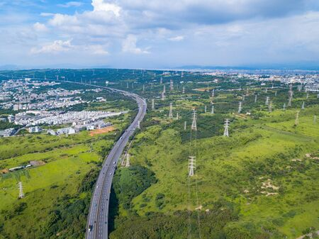 Aerial view of highways and high voltage metal post in the industrial estate. Electricity tower. Top view of green trees in forest landscape in Taichung Downtown, urban city, Taiwan. 版權商用圖片