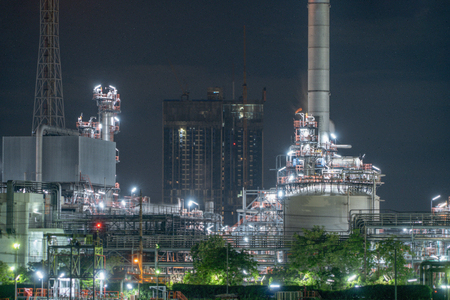 Petrochemical oil refinery and sea in industrial engineering concept in Bangna district, Bangkok, Thailand. Oil and gas tanks pipelines in industry. Modern metal factory at night.
