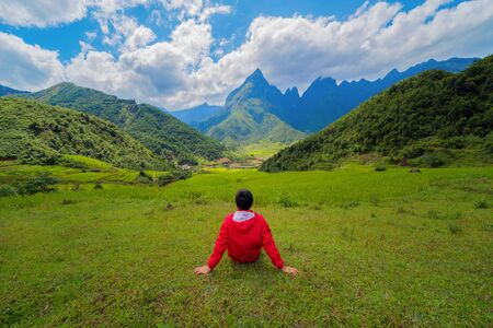 An Asian man watching at Fansipan mountain hills valley on summer in travel trip and holidays vacation concept, Vietnam.