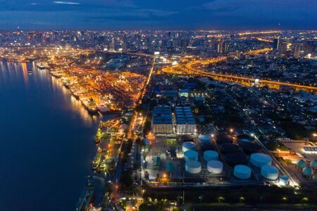 Aerial view of container cargo ship in the export, import business, logistics and transportation. International goods in urban city. Shipping to the harbor by crane in Bangkok City, Thailand at night. Stok Fotoğraf