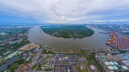 Aerial view of container cargo ship in the export, import business, logistics and transportation. International goods in urban city. Shipping to the harbor by crane in Bangkok City, Thailand.