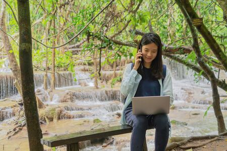 Happy Asian woman, a freelance, working and using a computer laptop notebook at waterfall in the tropical forest during travel trip and holidays vacation outdoors at national park, Thailand. Banque d'images - 132118697