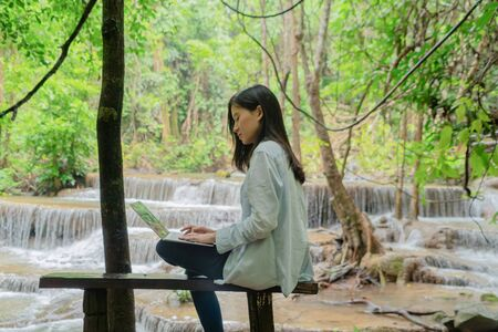 Happy Asian woman, a freelance, working and using a computer laptop notebook at waterfall in the tropical forest during travel trip and holidays vacation outdoors at national park, Thailand. Banque d'images - 132118657