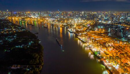 Aerial view of container cargo ship in the export, import business, logistics and transportation. International goods in urban city. Shipping to the harbor by crane in Bangkok City, Thailand at night. Stok Fotoğraf - 132117554