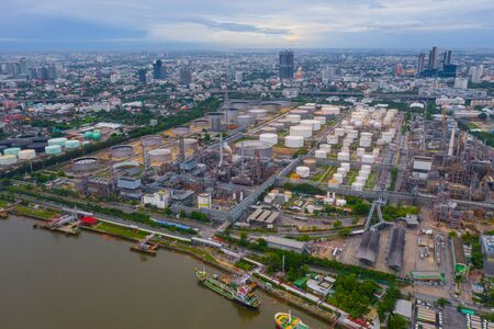 Aerial view of petrochemical oil refinery and sea in industrial engineering concept in Bangna district, Bangkok City, Thailand. Oil and gas tanks pipelines in industry. Modern metal factory.