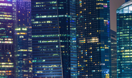 Pattern of office buildings windows illuminated at night. Lighting with Glass architecture facade design with reflection in urban city, Downtown Singapore City in financial district. Editorial