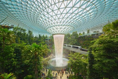 Jewel Changi Airport in Singapore City. Interior design decoration with waterfall, garden and trees. The worlds best airport and destination