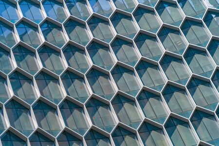 Office buildings. Structure of hexagon windows in futuristic technology network connection concept. Blue glass modern architecture facade design with reflection of sky in urban city, Downtown.