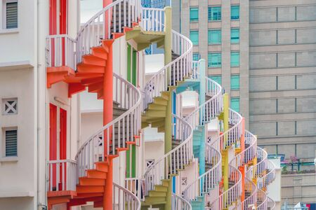 Close up of colorful pastel spiral staircases in Singapore, Bugis Village, vintage style fire exit of residential buildings, apartments, or houses.
