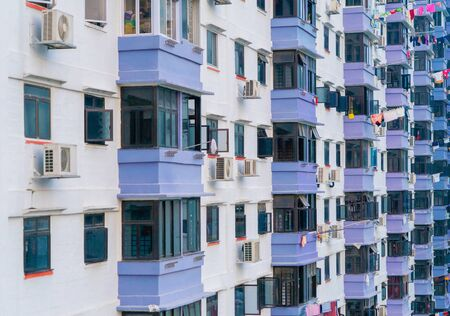 Pattern of old residential buildings, houses windows with clothes. Architecture facade design with reflection of sky in urban city, Singapore. Editorial