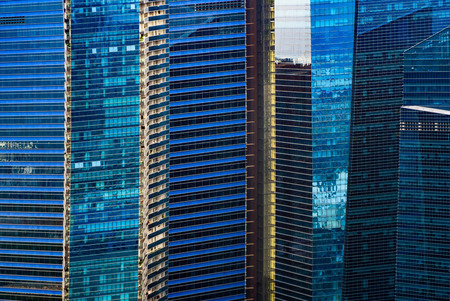 Office buildings windows. Blue glass architecture facade design with reflection of sky in urban city, Downtown Singapore City in financial district.