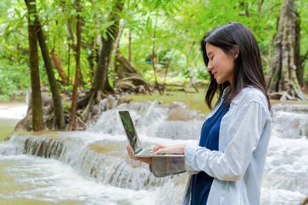 Happy Asian woman, a freelance, working online and using a computer laptop notebook at waterfall in the tropical forest during travel trip and holidays vacation outdoors at national park, Thailand. Banque d'images - 132117844