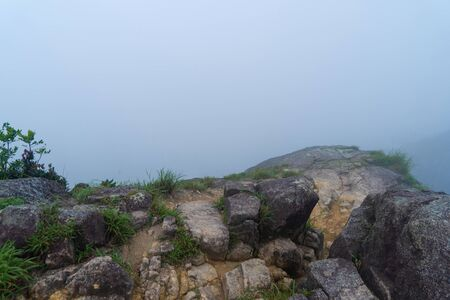 Stones on mountain or hill at the cliff peak of Lion Rock, Hong Kong in the morning with winter fog and copy space. Natural landscape background. White sky.