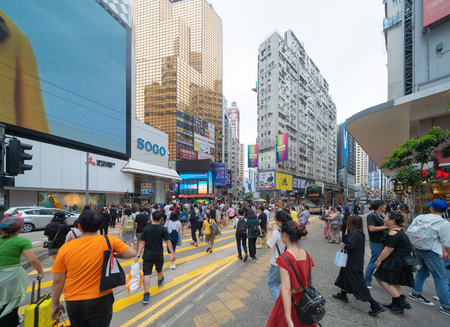 Crowd of people walking on street over zebra crossing or pedestrian crossing at shopping area with mall and department stores on street in Causeway Bay District, urban city of Hong Kong Downtown.