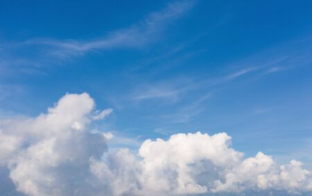 Clear blue sky with white fluffy clouds in summer season. Abstract nature background.