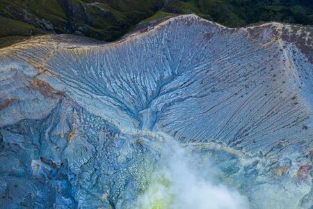 Aerial view of rock cliff at Kawah Ijen volcano with turquoise sulfur water lake at sunrise. Panoramic view at East Java, Indonesia. Natural landscape background. Stock Photo