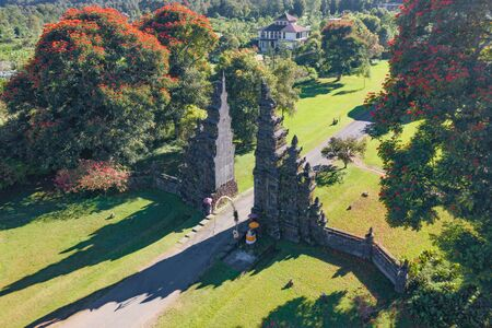 Aerial view of Bali Handara. The Hindu Temple with ancient gate with pathway in park garden at noon. Hindu architecture landscape background of travel trip and holidays vacation in Indonesia. 写真素材