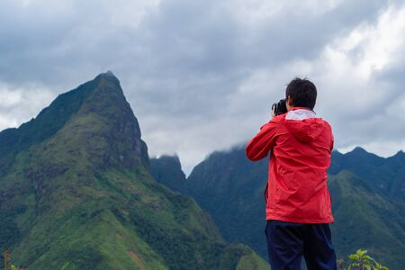 An Asian tourist man watching at Fansipan mountain hills with paddy rice agricultural field valley in summer in travel trip and holidays vacation concept, Sapa, Vietnam.
