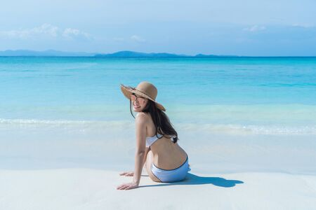 Happy Asian woman, a Thai lady, relaxing and enjoying at turquoise sea near Phuket beach in summer during travel holidays vacation trip outdoors at natural ocean or island at noon, Thailand. Stockfoto