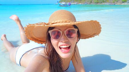 Happy Asian woman, a sexy Thai lady, using a mobile smartphone to share a live VDO to friends on social media at turquoise sea, Phuket beach in summer during travel holiday vacation trip, Thailand.