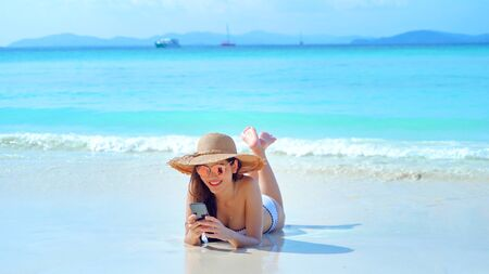 Happy Asian woman, a sexy Thai lady, using a mobile smartphone at turquoise sea near Phuket beach in summer during travel holidays vacation trip outdoors at natural ocean or island at noon, Thailand.