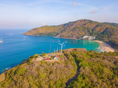 Aerial view of a wind turbine at Patong beach with blue turquoise seawater, and tropical green forest trees with Andaman sea in Phuket island in summer, Thailand in travel trip. Nature background.