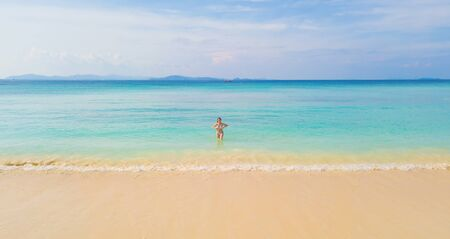 Happy Asian woman, a sexy Thai lady, relaxing and enjoying at turquoise sea near Phuket beach in summer during travel holidays vacation trip outdoors at natural ocean or island at noon, Thailand.