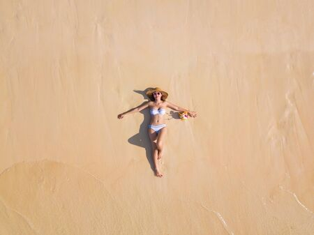 Aerial view of happy Asian woman, a sexy Thai lady, relaxing and enjoying at turquoise sea near Phuket beach in summer during travel holidays vacation trip outdoor at natural ocean or island, Thailand