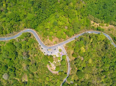 Aerial view of cars driving on curved, zigzag road or street way path on mountain hill with green natural green forest trees in Phuket City, Thailand. 写真素材