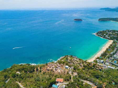 Aerial view of Patong beach with blue turquoise seawater, mountain hills, and tropical green forest trees with Andaman sea in Phuket island in summer, Thailand in travel trip. Nature background.