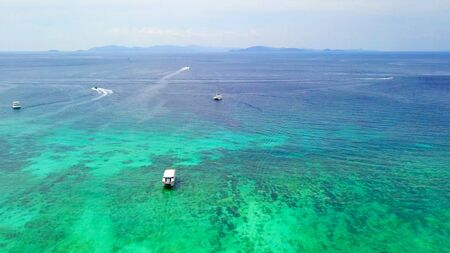 Aerial view of boats with clear blue turquoise seawater, Andaman sea in Phuket island in summer season, Thailand. Water in ocean material pattern texture wallpaper background.