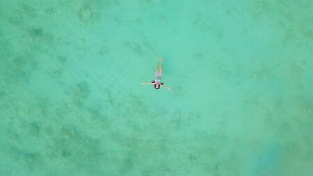 Aerial view of happy Asian woman, a sexy Thai lady, swimming at turquoise sea near Phuket beach in summer during travel holidays vacation trip outdoor at natural ocean or island, Thailand