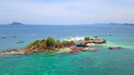 Aerial view of beach at Koh Khai, a small island, with crowd of people, tourists, blue turquoise seawater with Andaman sea in Phuket island in summer, Thailand in travel trip. Nature landscape.
