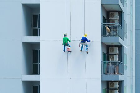 A company group of people, workers or painters, painting a wall on a high rise office building with cable wires outside in Bangkok Downtown, urban city at noon.