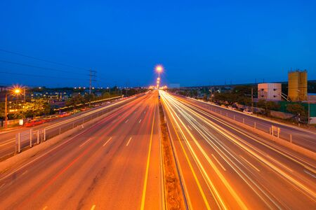 Car light trails on highway street or road in Bangkok, Thailand. Urban city at night in transportation, business, or technology concept. Wallpaper fast motion speed background. Long exposure. Stok Fotoğraf