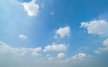 Clear blue sky with white fluffy clouds in summer season at noon time. Abstract nature background.