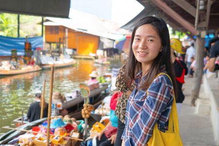 Portrait of Asian woman at Damnoen Saduak Floating Market in Ratchaburi District in travel trip and holidays vacation concept, Thailand. Famous tourist attraction.