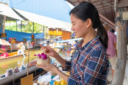 Asian woman eating coconut ice cream at Damnoen Saduak Floating Market in Ratchaburi District in travel trip and holidays vacation concept, Thailand. Famous tourist attraction.
