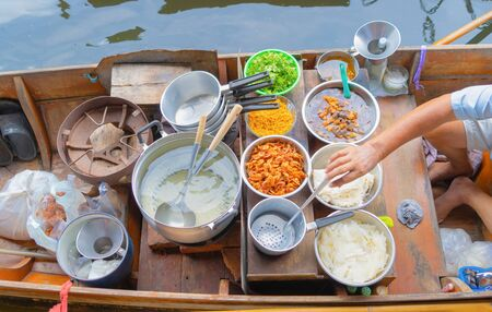 Local people sell fruits, food and souvenirs on boats at Damnoen Saduak Floating Market in Ratchaburi District, Thailand. Famous Asian tourist attraction.