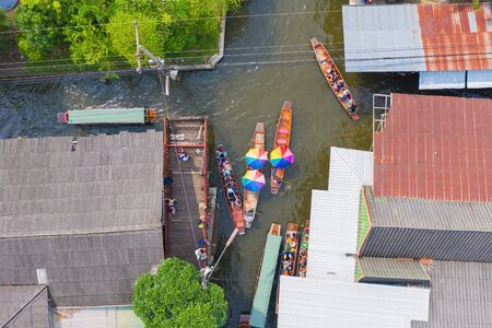 Aerial top view of local people sell fruits, food and souvenirs on boats at Damnoen Saduak Floating Market in Ratchaburi District, Thailand. Famous Asian tourist attraction.