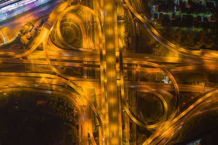 Aerial view of cars driving on highway junctions. Bridge roads shape number 8 or infinity sign in connection of architecture concept. Top view. Urban city, Bangkok at night, Thailand.