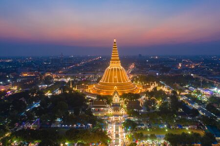 Aerial top view of Phra Pathommachedi temple at night. The golden buddhist pagoda with residential houses, urban city of Nakhon Pathom district, Thailand. Holy Thai architecture.