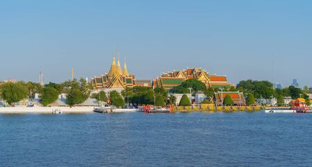 The Golden Grand Palace with the royal barge procession for The Thai King on Chao Phraya River near Downtown of Bangkok City, Thailand. Thai architecture buildings background. Big ceremony.
