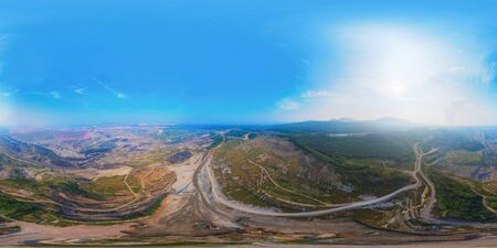 360 panorama by 180 degrees angle seamless panorama of aerial view of machine excavator trucks dig coal mining or ore in quarry with mountain hills. Nature landscape background in factory industry