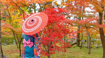 An Asian woman wearing Japanese traditional kimono with red umbrella standing with Red maple leaves or fall foliage in Autumn season during travel holidays vacation trip outdoors in Kyoto City, Japan. Stok Fotoğraf