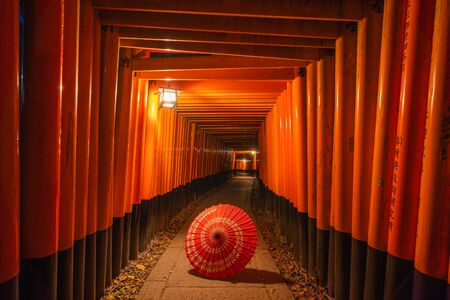 Traditional red Japanese umbrella in Fushimi Inari Taisha in travel holidays vacation trip outdoors concept in Kyoto, Japan. Red poles in the temple. Walkway tunnel of shrine.